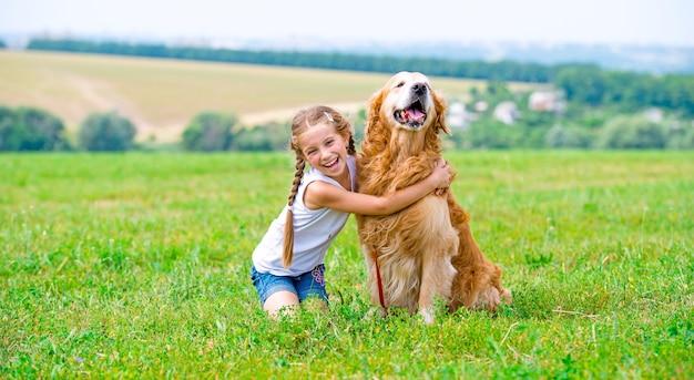 Kleines mädchen mit goldenem apportierhund