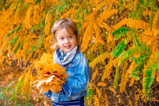 Kleines mädchen mit goldenen blättern des gelben herbstes. kinderspiel draußen im park.