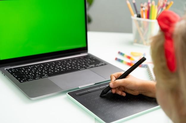 Kleines mädchen mit grafiktablett und laptop moderne grafikdesignkurse für schulkinder für