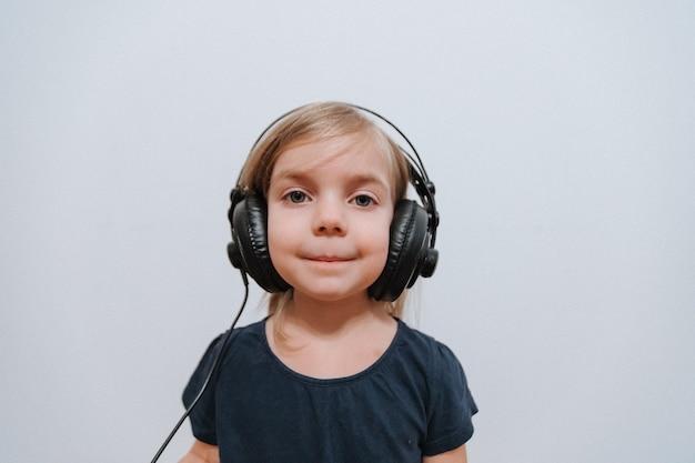 Kleines mädchen mit großen kopfhörern zu hause