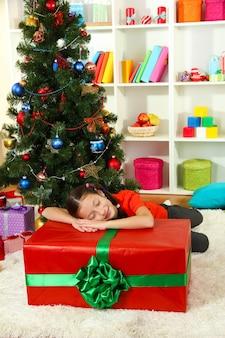 Kleines mädchen mit großer geschenkbox in der nähe von weihnachtsbaum