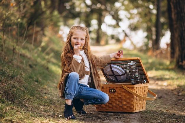 Kleines mädchen mit großer picknickbox im wald