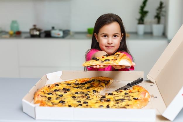 Kleines mädchen mit großer pizza zu hause