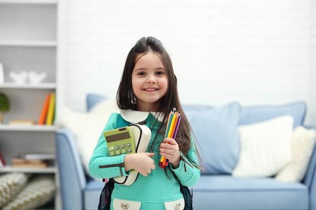Kleines mädchen mit grünem rucksack, der briefpapier und taschenrechner im wohnzimmer hält