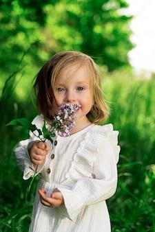 Kleines mädchen mit grünen augen in einem grünen garten mit einer lila blume schaut in den rahmen