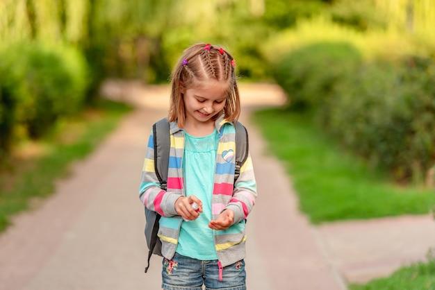 Kleines mädchen mit händedesinfektionsmittel nach der schule im park