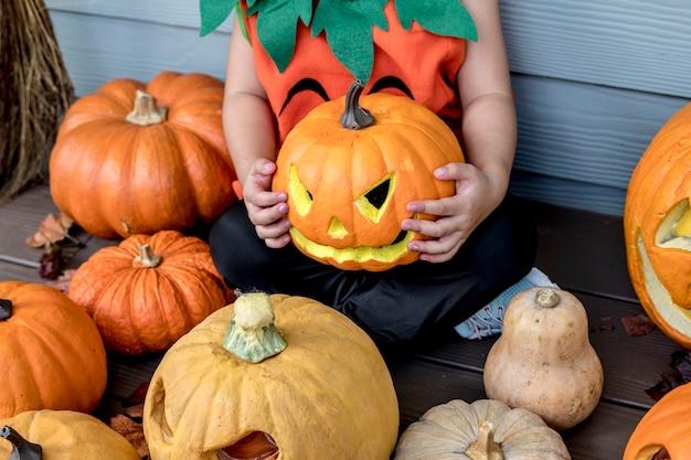Kleines mädchen mit halloween-kürbissen