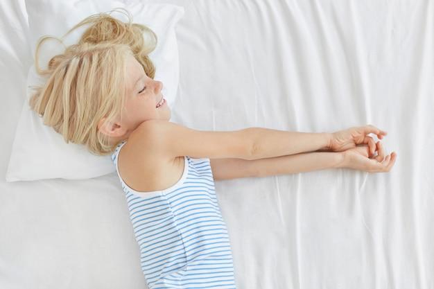 Kleines mädchen mit hellem haar, das gute nacht auf weißer bettwäsche hat, von etwas träumt, angenehm lächelt. mädchen, das träume im bett hat. kinder, kindheit, entspannung und lifestyle-konzept