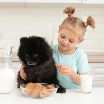 Kleines mädchen mit hund, der milch trinkt