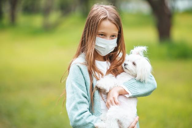 Kleines mädchen mit hund mit medizinischer schutzmaske zur vorbeugung von viren im freien im park