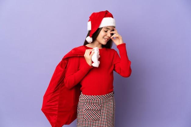 Kleines mädchen mit hut und weihnachtssack auf violettem hintergrund lachend