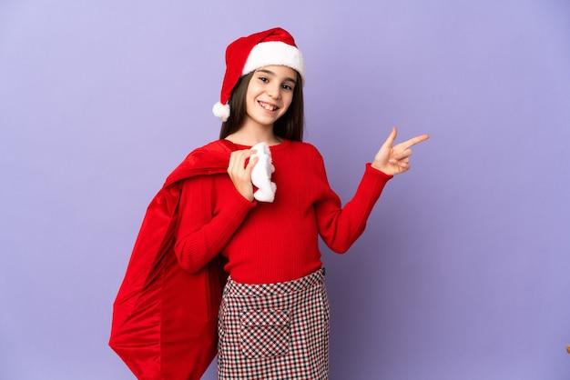 Kleines mädchen mit hut und weihnachtssack lokalisiert auf lila wand, die finger zur seite zeigt