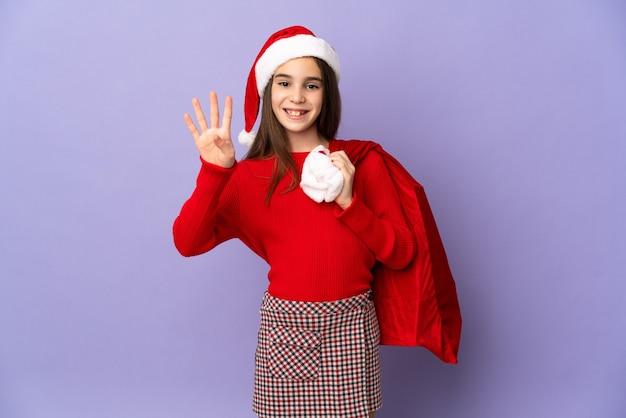 Kleines mädchen mit hut und weihnachtssack lokalisiert auf lila wand glücklich und zählt vier mit den fingern