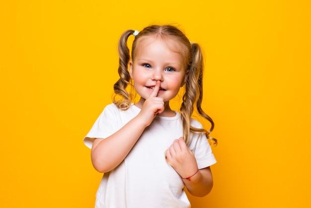 Kleines mädchen mit ihrem finger über mund, der shh lokalisiert über gelber wand sagt