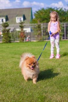 Kleines mädchen mit ihrem hund an der leine spazieren
