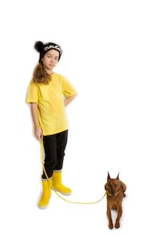 Kleines mädchen mit ihrem hund, schwarze und gelbe kleidung. weißer hintergrund. studioaufnahmen. konzept für baby-haustiere. foto in hoher qualität