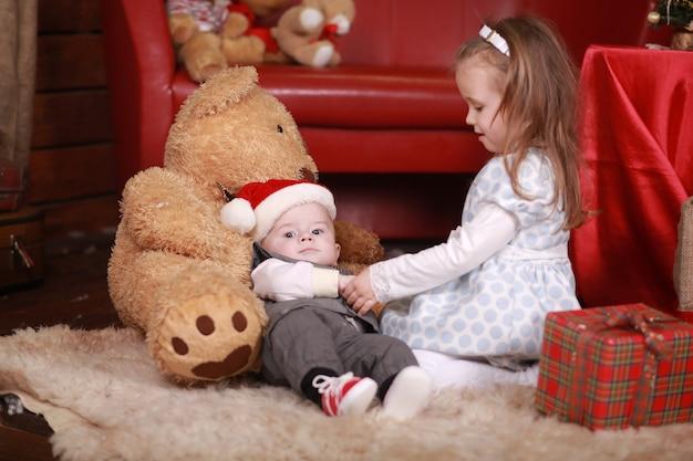 Kleines mädchen mit ihrem kleinen bruder, der nahe einem weihnachtsgeschenk sitzt. neujahr. familie, glück, feiertage, weihnachtskonzept.