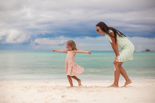 Kleines mädchen mit ihrer mutter, die am weißen sandigen strand an einem sonnigen tag tanzt