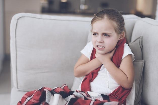 Kleines mädchen mit kälte hat halsschmerzen auf der couch.