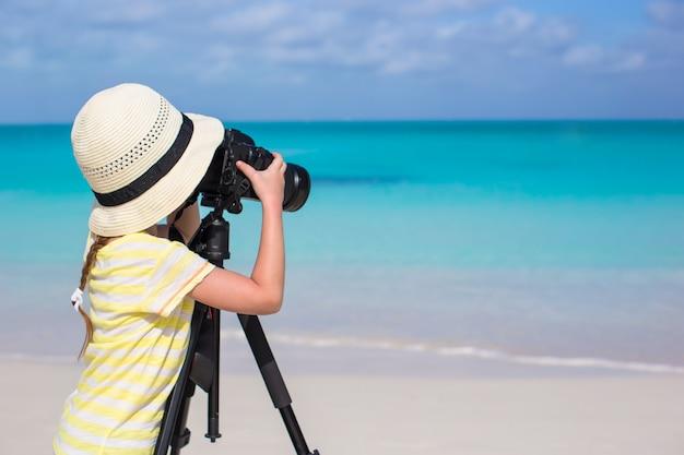 Kleines mädchen mit kamera auf einem stativ am weißen sandigen strand