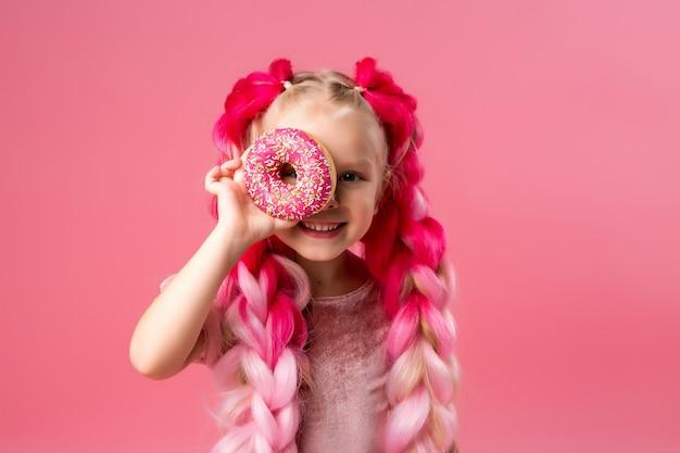 Kleines mädchen mit kanekalon zöpfen mit donuts auf rosa hintergrund