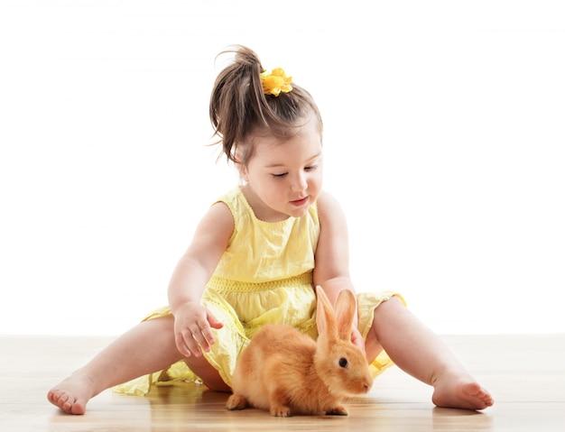Kleines mädchen mit kaninchen lokalisiert auf weiß