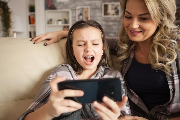Kleines mädchen mit klammern und ihre mutter sitzen auf der couch im wohnzimmer und schauen sich cartoon im wohnzimmer an.