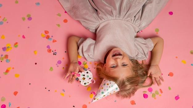 Kleines mädchen mit konfetti und partyhut