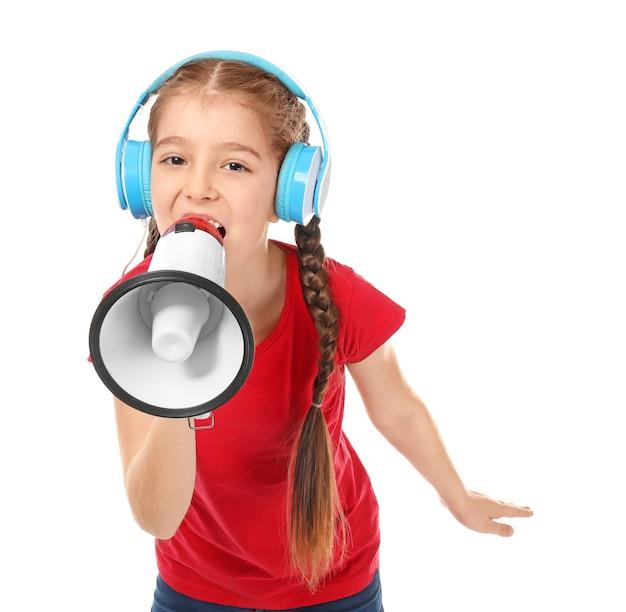 Kleines mädchen mit kopfhörern, die in megaphon auf weiß schreien