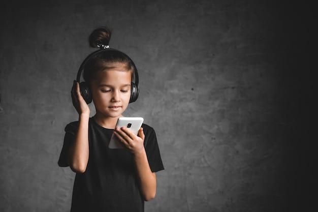 Kleines mädchen mit kopfhörern und telefon auf grauem hintergrund