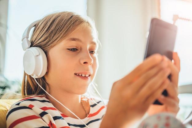 Kleines mädchen mit kopfhörern unter verwendung des intelligenten telefons