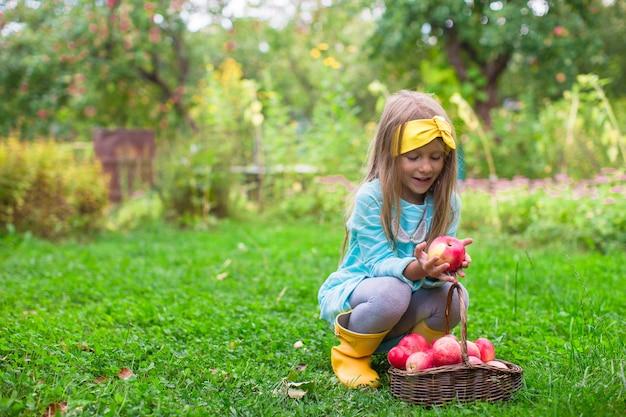 Kleines mädchen mit korb von äpfeln am sonnigen herbsttag