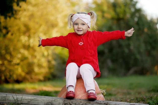 Kleines mädchen mit kürbis im herbstpark
