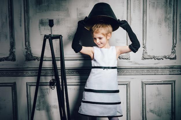 Kleines mädchen mit lampenschirmhut im kleid. kind in einem eleganten glamourösen kleid und handschuhen. retro mädchen, model, schönheit. retro, friseur, make-up, pin up. mode, pinup-stil, kindheit