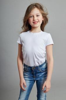Kleines mädchen mit langen blonden haaren und in jeans, die auf einem weißen hintergrund aufwerfen. freude spaß, junge modell kinder mode. modellschule für kinder.