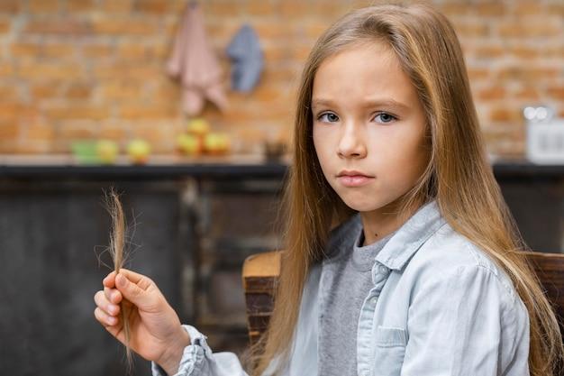 Kleines mädchen mit langen haaren hält, was sie am friseur geschnitten hat