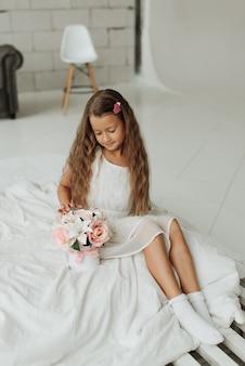 Kleines mädchen mit langen haaren und einem blumenstrauß sitzt auf einem weißen bett