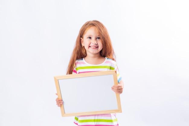 Kleines mädchen mit langen roten haaren lächelt und hält ein weißes zeichenbrett