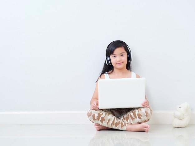 Kleines mädchen mit laptop, der auf boden sitzt.