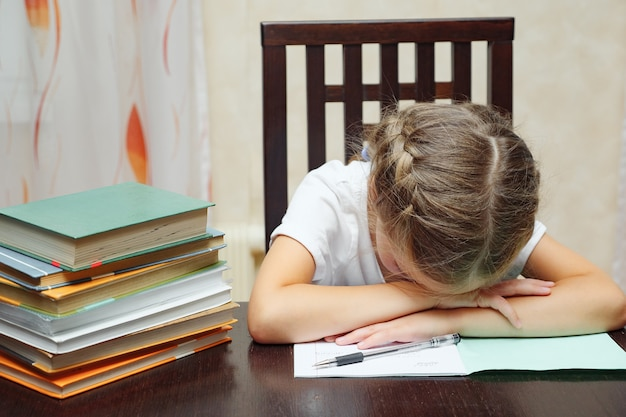 Kleines mädchen mit lehrbüchern, das schlafend studiert