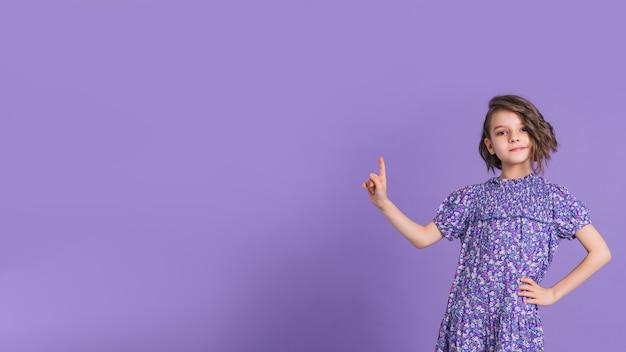 Kleines mädchen mit lila kleid nach oben auf lila hintergrund