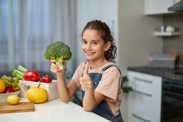 Kleines mädchen mit lockigem haar, das einen brokkoli hält und in die kamera schaut, einen daumen zeigt, sitzt am tisch in der küche.