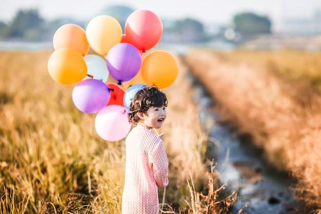 Kleines mädchen mit luftballons auf weizenfeld spielen