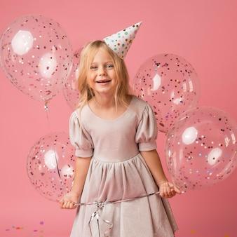 Kleines mädchen mit luftballons und partyhut