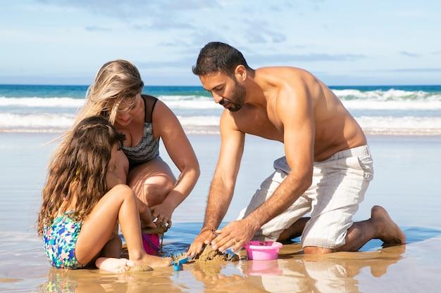 Kleines mädchen mit mama und papa, die urlaub auf see genießen, mit spielzeug auf nassem sand und im wasser spielend