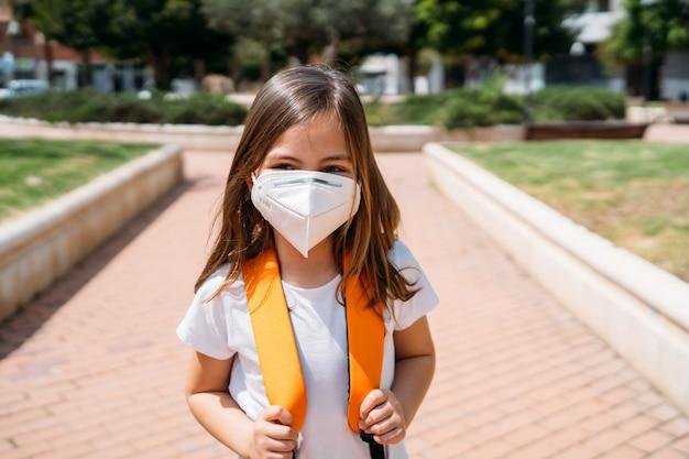 Kleines mädchen mit maske in einem park während der coronavirus-pandemie