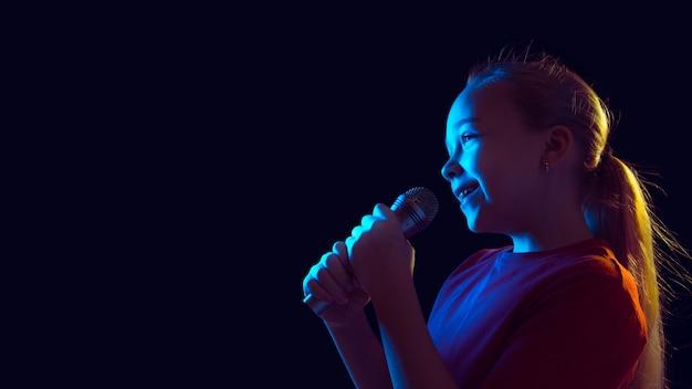 Kleines mädchen mit mikrofon im neonlicht