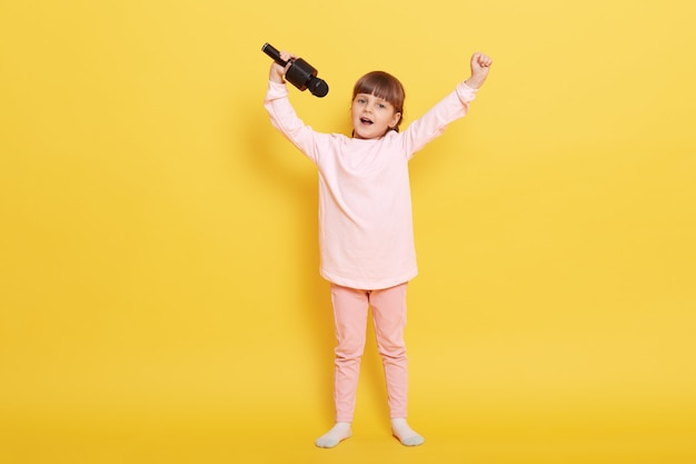 Kleines mädchen mit mikrofon singt vor gelbem farbhintergrund, hält hände hoch, arrangiert konzerte, tritt für jemanden auf, singt im karaoke, kind mit zöpfen trägt lässig.