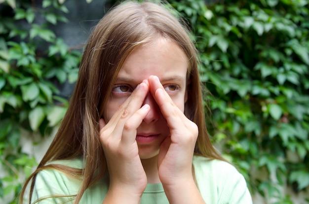 Kleines mädchen mit nebenhöhlen- und ohrschmerz. kind, das nasales gesundheitsproblem hat