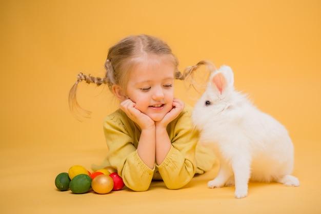 Kleines mädchen mit osterhasen auf gelbem grund